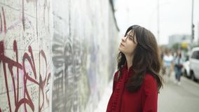 Beautiful young woman near the Berlin wall, pan shot. Beautiful young woman with dark hair wearing a red shirt is looking at the Berlin wall on a sunny summer stock video