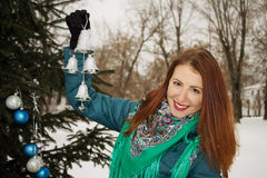 Beautiful young woman decorates a Christmas tree in the garden. Stock Image
