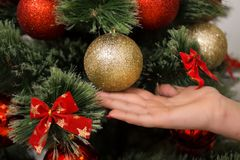 Beautiful young woman decorating a Christmas tree.  Stock Photo