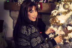 Beautiful young woman decorating a Christmas tree Stock Image