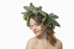 Portrait of beautiful young woman with Christmas wreath on a whi Stock Photography