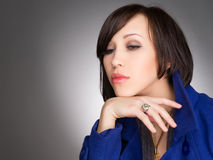 Beautiful young woman deep in thoughts. Wearing dark blue winter coat. Studio portrait. Royalty Free Stock Photography