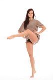Beautiful young woman demonstrating dance moves. Beautiful young female dancer with one leg raised, toe pointed, striking pose on white back ground. Elegant Stock Photo