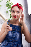 Beautiful young woman in denim overalls and a bandana looking at the camera as the mirror, Chupa Chups licking and Stock Image