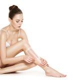 Beautiful young woman depilating legs by waxing Stock Photos