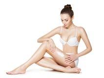Beautiful young woman depilating legs by waxing Royalty Free Stock Photo