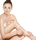 Beautiful young woman depilating legs by waxing Stock Images