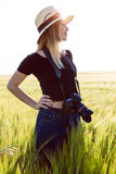 Beautiful young woman with digital camera taking photos in a field. Royalty Free Stock Photo