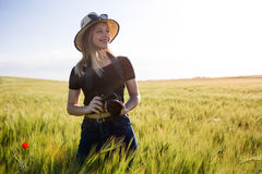 Beautiful young woman with digital camera taking photos in a field. Royalty Free Stock Photos