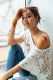Beautiful young woman dirty with paints sitting near the window Stock Image