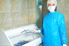 Beautiful young woman doctor gets sterile items required for ope Royalty Free Stock Photo