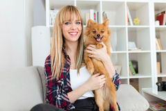 Beautiful young woman with dog playing at home. Stock Images