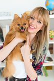 Beautiful young woman with dog playing at home. Stock Image
