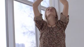 Beautiful young woman doing breathing exercises before practicing yoga stock video footage