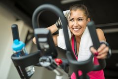 Beautiful young woman doing cardio on a stationary bike. While smiling stock images