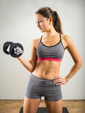 Beautiful young woman doing dumbbell curl. Photo of an attractive woman doing a dumbbell curl while standing Royalty Free Stock Images