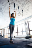 Beautiful young woman doing exercise on gimnastic rings Royalty Free Stock Photography