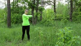 Beautiful young woman doing exercise in park summer day stock video footage