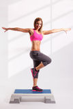 Beautiful young woman doing exercises. On aerobic step Royalty Free Stock Images