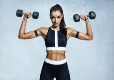 Beautiful young woman doing exercises with dumbbells stock images