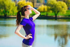 Beautiful young woman doing fitness exercise on a beach. Sports girl in a blue T-shirt and sun glasses looks into the distance Stock Image