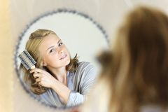 Beautiful young woman doing hair with hairbrush Royalty Free Stock Image