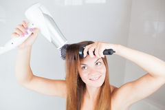 Beautiful young woman doing hairstyle Stock Photos