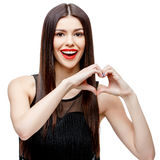 Beautiful young woman doing a heart shape with her hands Stock Photo