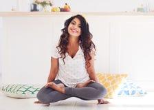 Beautiful young woman doing Kukkutasana Yoga Cockerel pose at home stock image