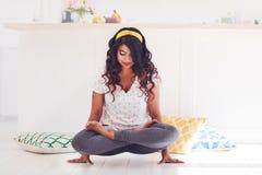 Beautiful young woman doing Kukkutasana Yoga Cockerel pose at home stock photo