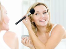 Beautiful young woman doing make-up Stock Photography