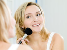 Beautiful young woman doing make-up Stock Photo