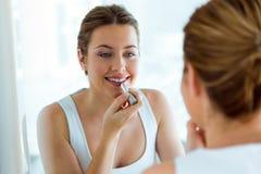Beautiful young woman doing make-up near mirror at home. Portrait of beautiful young woman doing make-up near mirror at home Stock Photography