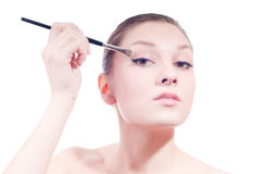 Beautiful young woman doing makeup isolated Stock Photography
