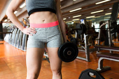 Beautiful young woman doing muscular exercise in gym. Stock Photography