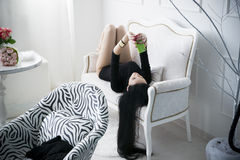 Beautiful young woman doing selfie lying on the sofa Royalty Free Stock Photos