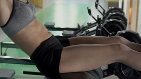 The beautiful young woman is doing sit-ups in the gym using special equipment. The beautifel young woman is doing sit-ups in the gym using special equipment stock video footage
