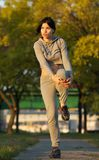 Beautiful young woman doing stretch exercises outdoors Stock Photos