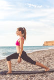 Beautiful young woman doing stretching on the beach Royalty Free Stock Photo