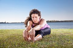 Beautiful young woman doing stretching exercise on green grass. Royalty Free Stock Photography