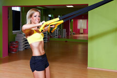 Beautiful young woman doing TRX exercise Royalty Free Stock Images