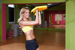 Beautiful young woman doing TRX exercise Royalty Free Stock Photos