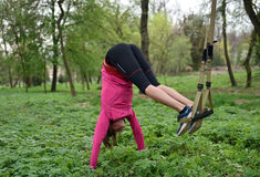 Beautiful young woman doing TRX exercise with suspension trainer stock image