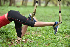Beautiful young woman doing TRX exercise with suspension trainer stock photos