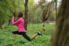 Beautiful young woman doing TRX exercise with suspension trainer royalty free stock photography