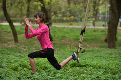 Beautiful young woman doing TRX exercise with suspension trainer royalty free stock image