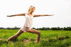 Beautiful young woman doing yoga exercise on field. Stock Photos