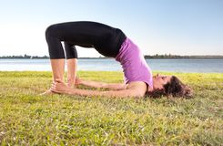 Beautiful young woman doing yoga exercise on green grass Royalty Free Stock Images