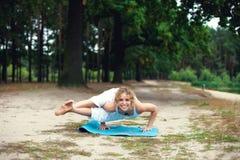Beautiful young woman doing yoga exercise outdoors Stock Image