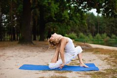 Beautiful young woman doing yoga exercise outdoors Stock Photography